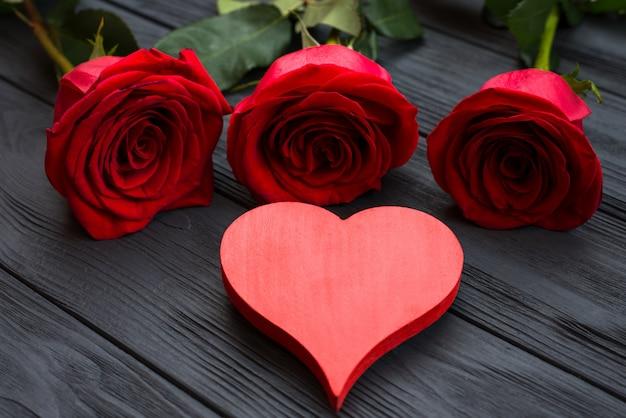 Czerwone serce i czerwone róże na ciemnej drewnianej powierzchni