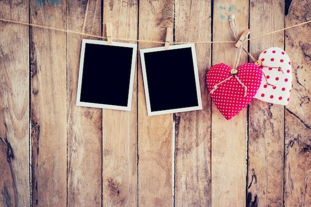 Czerwone serce i dwie ramki na wieszak na sznurku z drewnianym tłem.