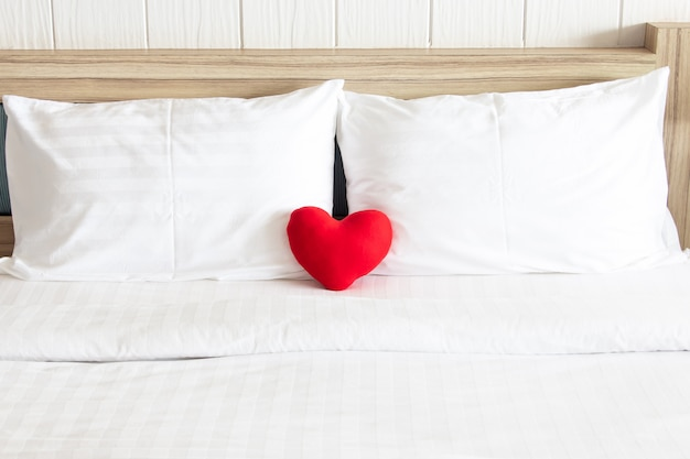 Czerwone serce i para biała poduszka na łóżku dla miłości, ślubu i walentynki koncepcji
