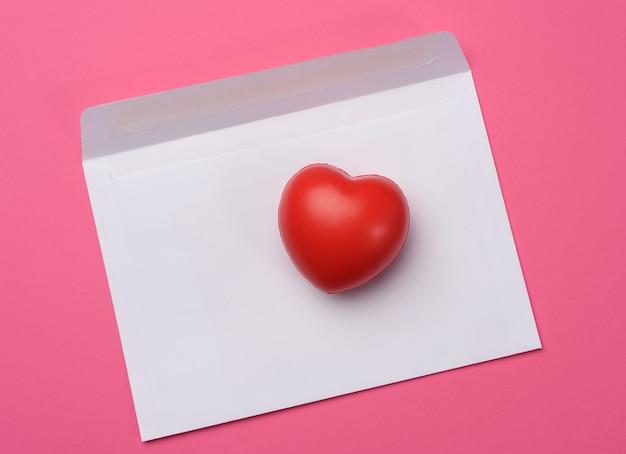 Czerwone serce i pusty biały papier na różowym tle, widok z góry