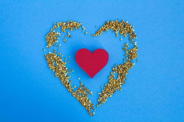 Czerwone serce i pyłek pszczeli na niebiesko