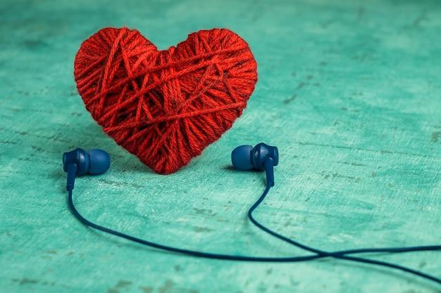 Czerwone serce i słuchawki. słuchanie ulubionej muzyki