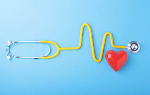 Czerwone serce i stetoskop na niebieskim tle