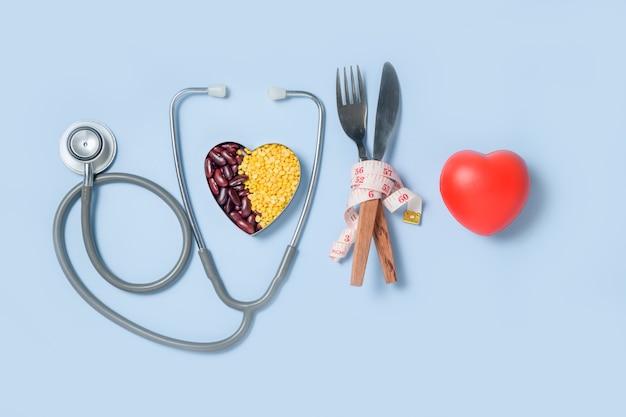 Czerwone serce i stetoskop z miarką wokół widelca i noża oraz soja i czerwona fasola w formie w kształcie serca na białym tle, koncepcja opieki zdrowotnej i diety