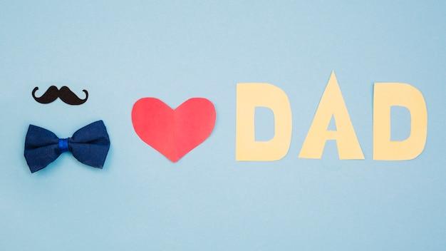 Czerwone serce i tytuł taty w pobliżu muszki i wąsy