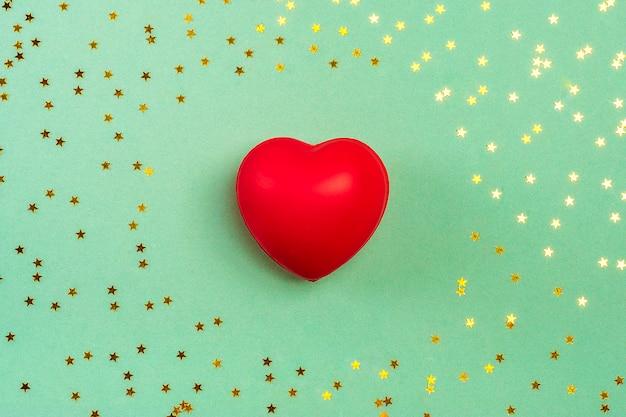 Czerwone serce i złote świecidełka w kształcie gwiazd na zielonym tle.