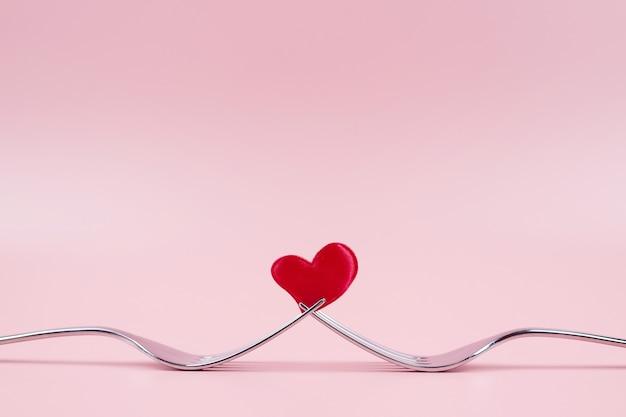 Czerwone serce między dwoma widelcami, na różowym tle. koncepcja walentynki