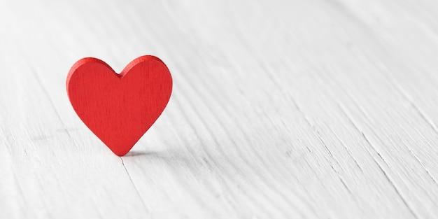 Czerwone serce na białym drewnianym stole