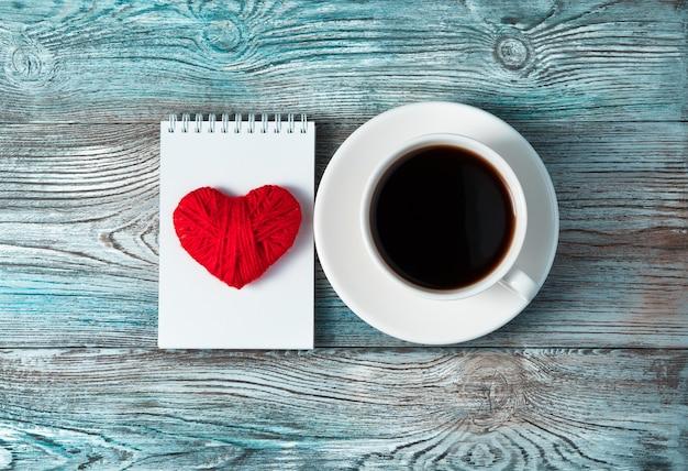 Czerwone serce na białym notatniku i filiżankę kawy na drewnianym szaro-niebieskim tle.