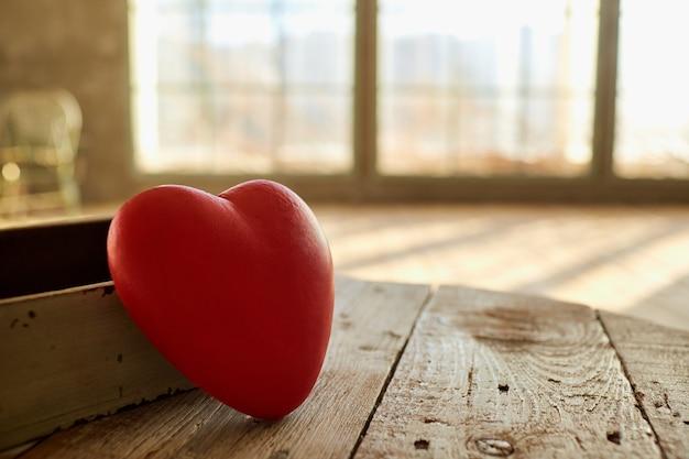 Czerwone serce na drewnianym stole przed oknem