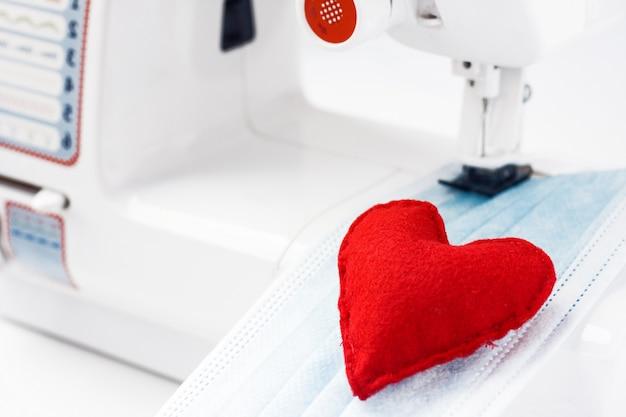 Czerwone serce na masce na twarzy. ochrona zdrowia i koronawirus chronią za pomocą maski szyjącej. szycie masek medycznych w celu ochrony przed koronawirusem.