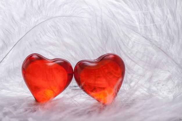 Czerwone serce na tle białych piór