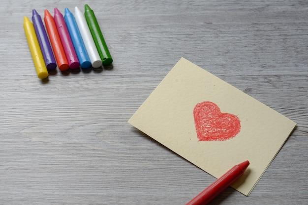 Czerwone serce narysuj na papierze notatkę z kolorowym kredkami woskowymi