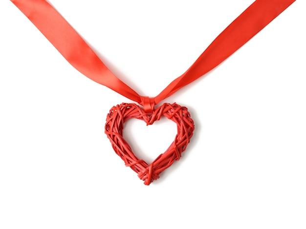 Czerwone serce plecione i skręcone jedwabne wstążki na białym tle, z bliska