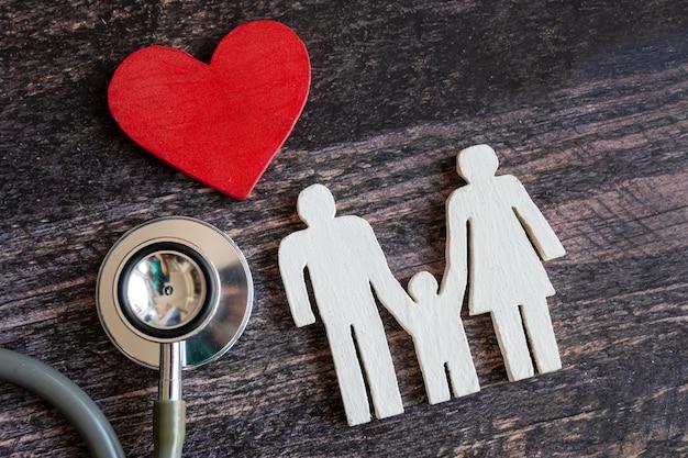 Czerwone serce, stetoskop i ikona rodziny na drewniane biurko. pojęcie ubezpieczenia medycznego