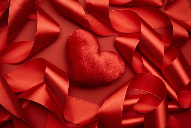 Czerwone serce tekstylne i zwinięte czerwoną wstążką jedwabną na czerwonym tle, świąteczne tło, widok z góry