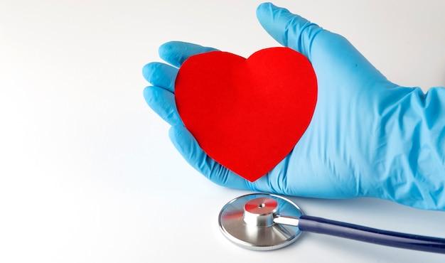 Czerwone serce w dłoni lekarza ze stetoskopem medycznym