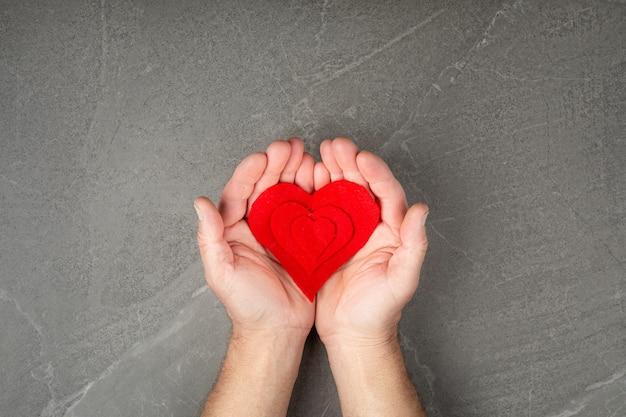 Czerwone serce w dłoniach na szarej ścianie, koncepcja miłości i troski o bliskich i potrzebujących.