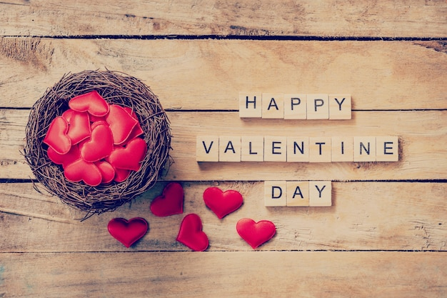 Czerwone serce w gnieździe z drewnianym tekstem happy valentine day na tle drewna tabeli.