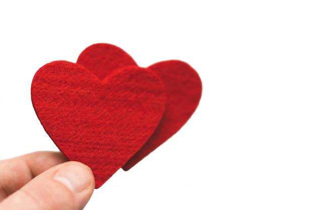 Czerwone serce w palcach na białym tle. walentynki