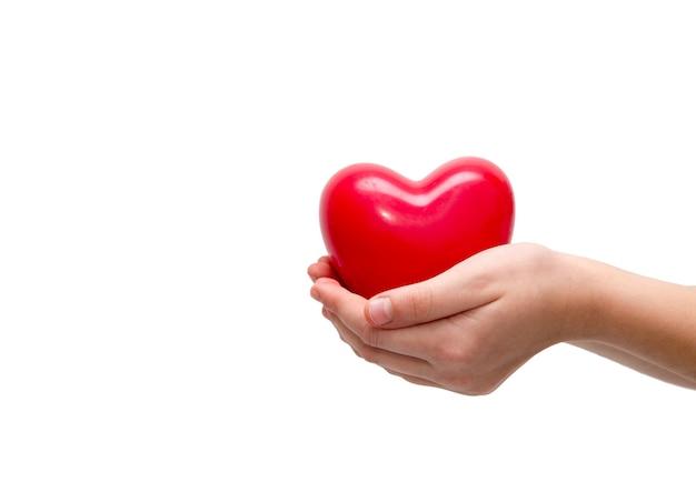 Czerwone serce w ręce kobiety na białym tle