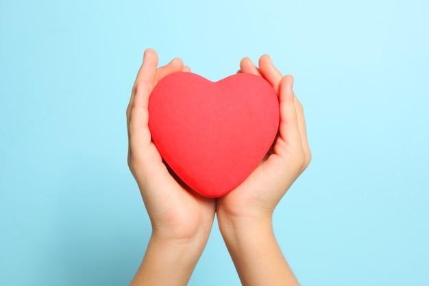 Czerwone serce w rękach dzieci na niebieskim tle z bliska