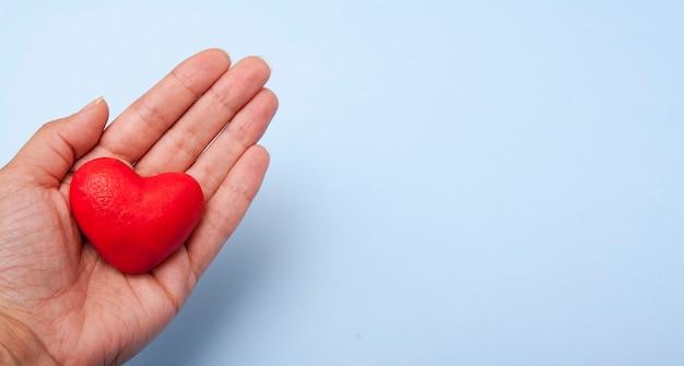 Czerwone serce w ręku na niebiesko z miejsca na kopię.