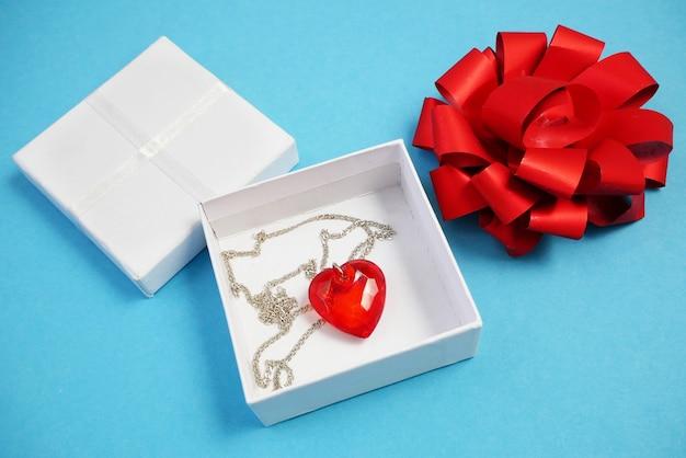 Czerwone serce wisiorek z przezroczystym kamieniem w pudełku na niebiesko