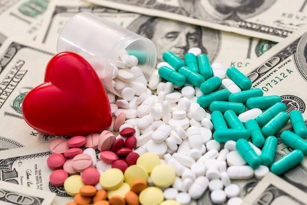 Czerwone serce z kolorowych tabletek na banknotach dolarowych