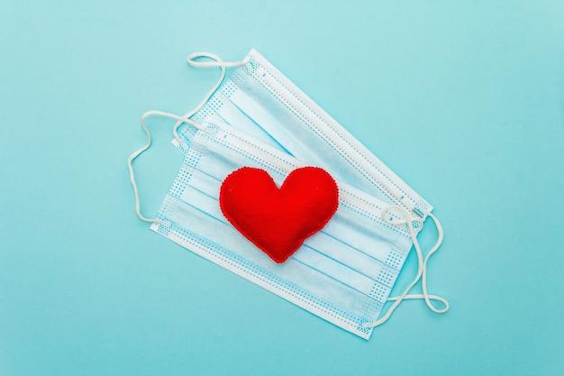 Czerwone serce z maskami ochrony medycznej na jasnoniebieskim tle, widok z góry, miejsce. pojęcie opieki zdrowotnej, samoobrony