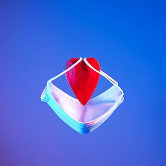 Czerwone serce z ochronną maską w neonowym świetle. koncepcja walentynki