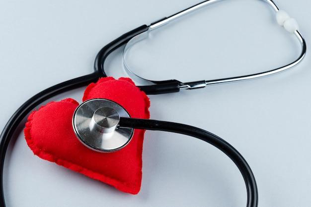 Czerwone serce z stetoskop na szarej ścianie. pojęcie ubezpieczenia zdrowotnego.