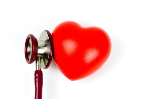 Czerwone Serce Ze Stetoskopem Na Białym Tle Selekcyjna Ostrość. Koncepcja Opieki Zdrowotnej Premium Zdjęcia