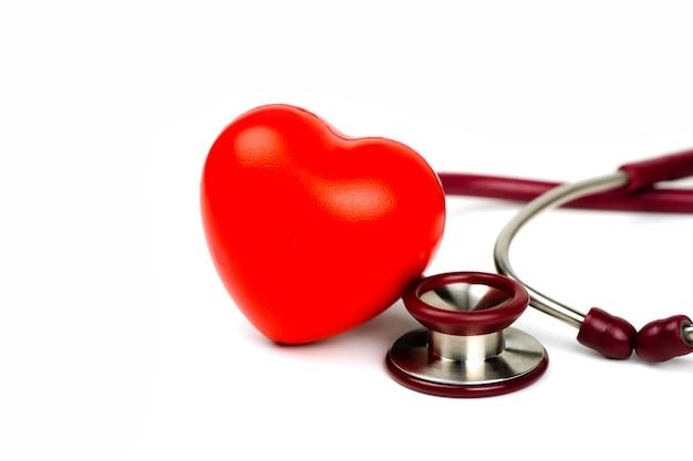 Czerwone serce ze stetoskopem na białym tle selekcyjna ostrość. koncepcja opieki zdrowotnej