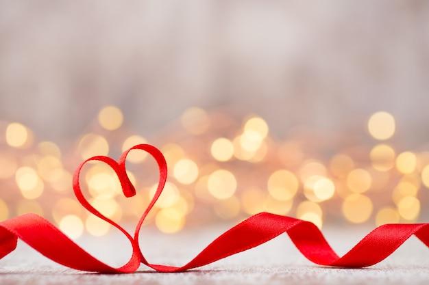 Czerwone serce ze wstążką. walentynki-dzień tło.