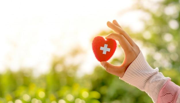 Czerwone serce ze znakiem krzyża reprezentuje symbol opieki zdrowotnej.