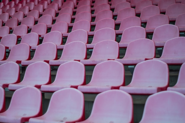Czerwone siedzenia na stadionie. puste miejsce na stadionie piłkarskim.