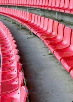 Czerwone siedzenia stadionowe po deszczu. trybuna piłkarska, piłkarska lub stadion baseballowy bez fanów