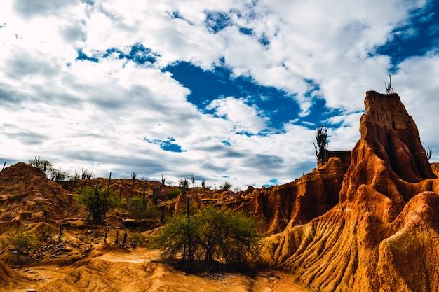 Czerwone skały i egzotyczne rośliny na pustyni tatacoa w kolumbii pod zachmurzonym niebem