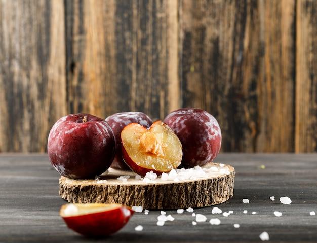 Czerwone śliwki z solą na drewnianym kawałku na drewnianej i szarej powierzchni, boczny widok.