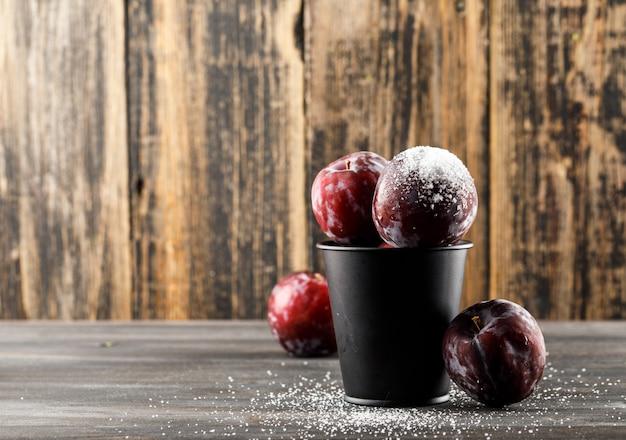Czerwone śliwki z solą w mini wiadrze na drewnianej i szarej powierzchni, widok z boku.