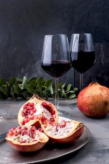 Czerwone słodkie jagody na zabytkowym metalowym naczyniu i nożu, dwie szklanki czerwonego wina