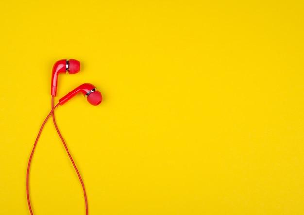 Czerwone słuchawki douszne na jasnym żółtym tle
