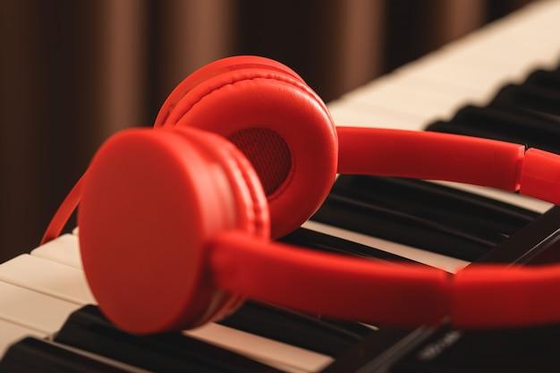 Czerwone słuchawki nad klawiaturą syntezatora