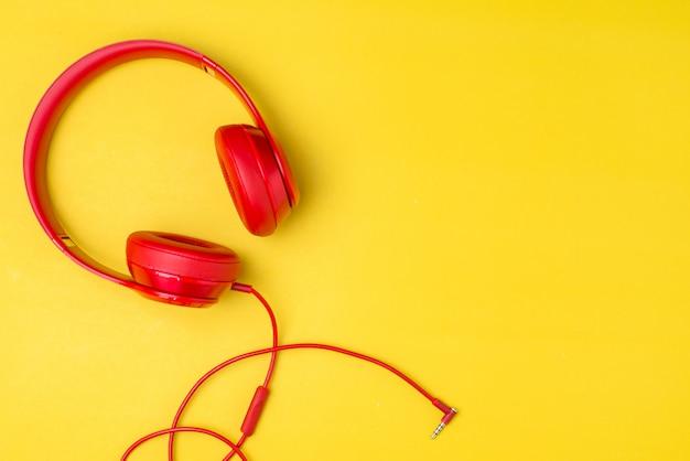Czerwone słuchawki słuchają muzyki na smartfonie na żółtym tle.