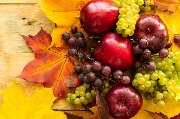 Czerwone soczyste dojrzałe jabłka i winogrona na drewnianym tle
