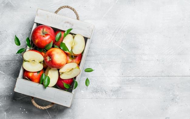 Czerwone soczyste jabłka i plasterki jabłka w drewnianym pudełku.