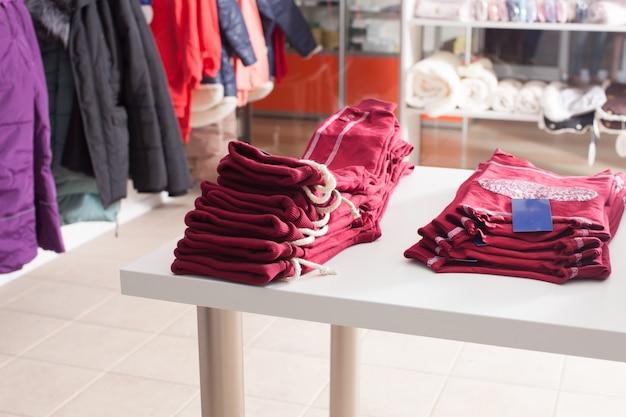 Czerwone spodnie ułożone w rzędy na białej półce w sklepie odzieżowym