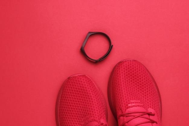 Czerwone sportowe buty do biegania i inteligentna bransoletka xaon na czerwonym tle papieru