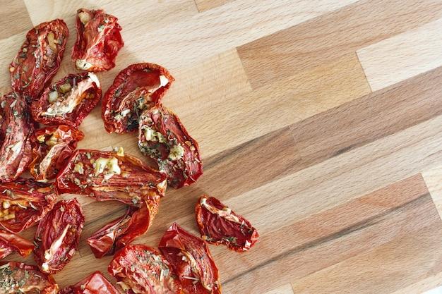 Czerwone suszone pomidory z czosnkiem i ziołami prowansalskimi na drewnianej powierzchni